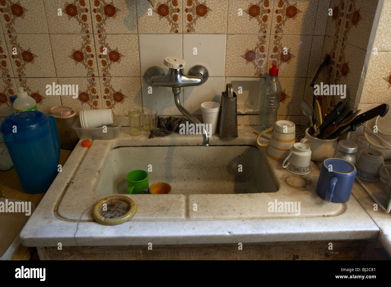 old crowded kitchen sink in a dirty run down kitchen in south ...