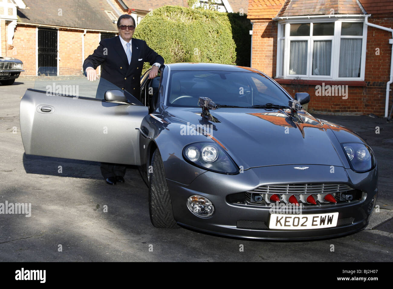SIR ROGER MOORE WITH THE ASTON MARTIN VANQUISH FROM THE