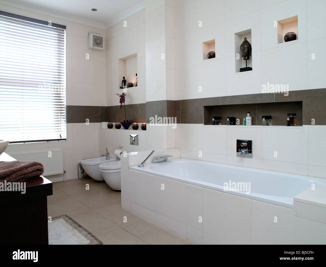 Modern bathrooms tiled in white and brown tiles,his and hers wash ...