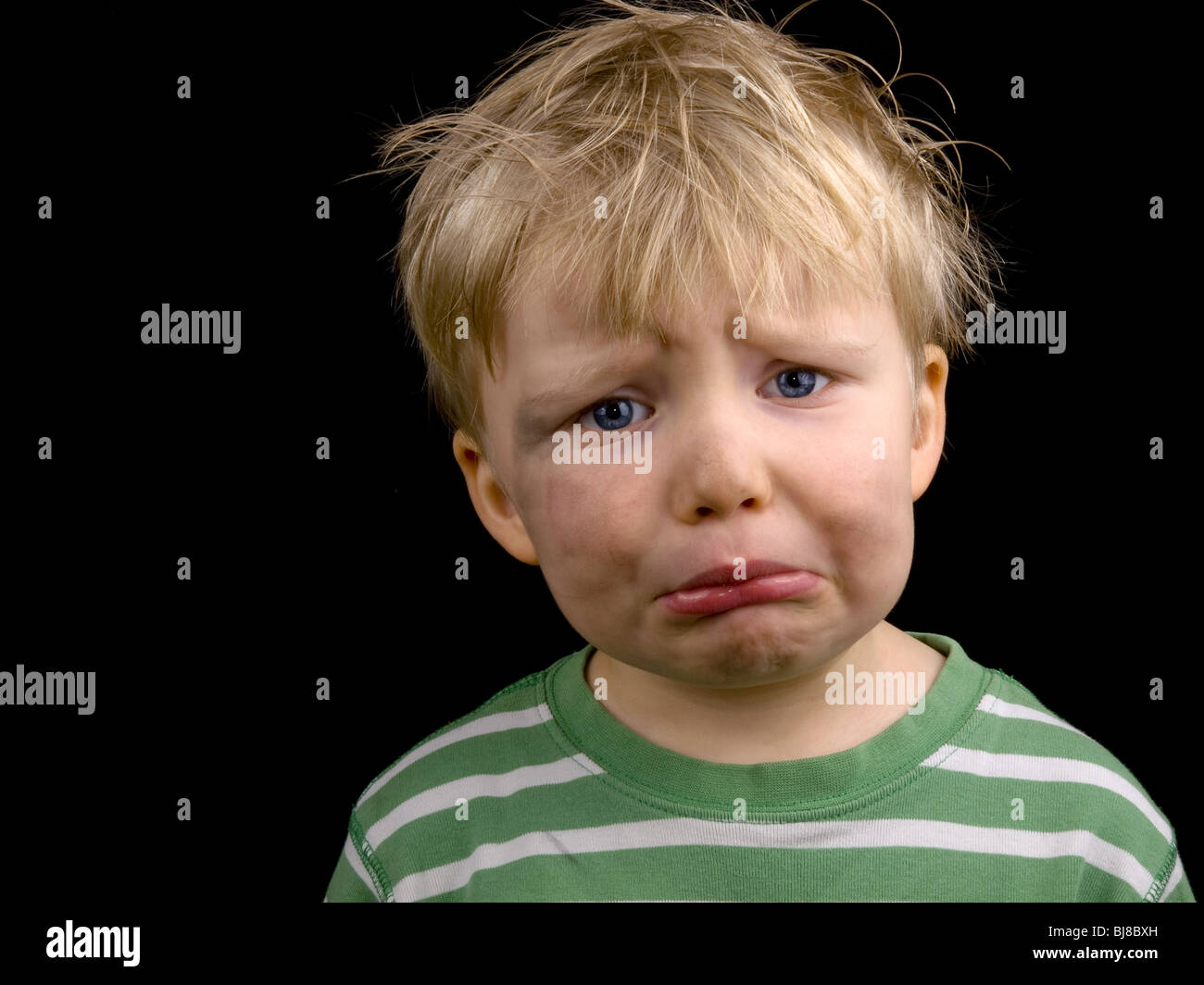 very sad little boy on black background boy have blond