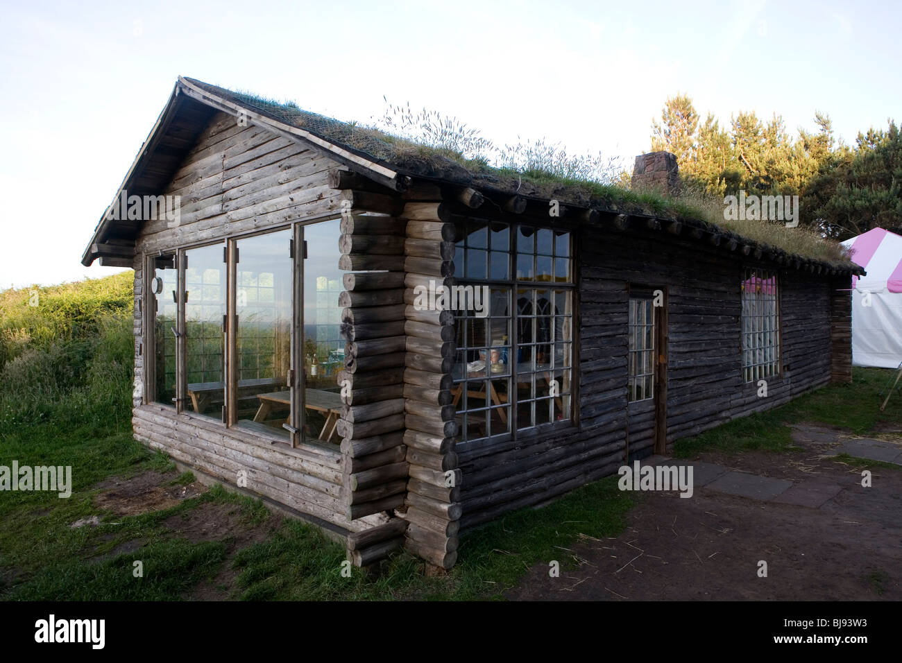 wooden country cottage with turfed roof and large windows party tent in the background & wooden country cottage with turfed roof and large windows party ...