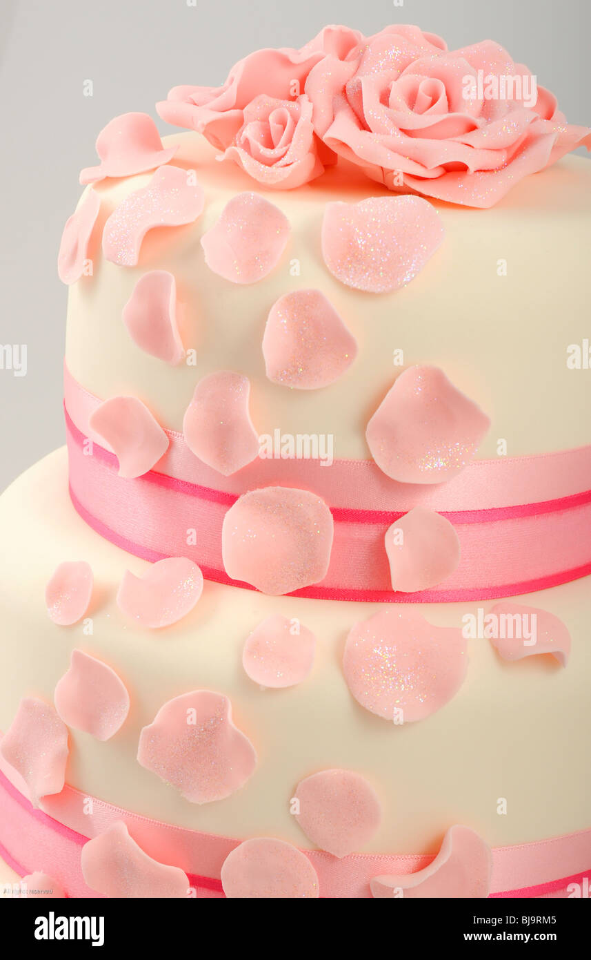 Close Up Of Tiered Wedding Cake With Pink Flowers And Petals Falling Down