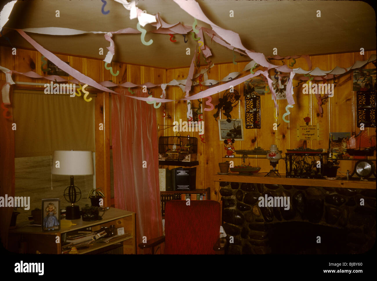 A Room Inside A House With Wood Panel Walls Is Decorated For A New Years  Party During The Late 1950s. Celebration Ribbons