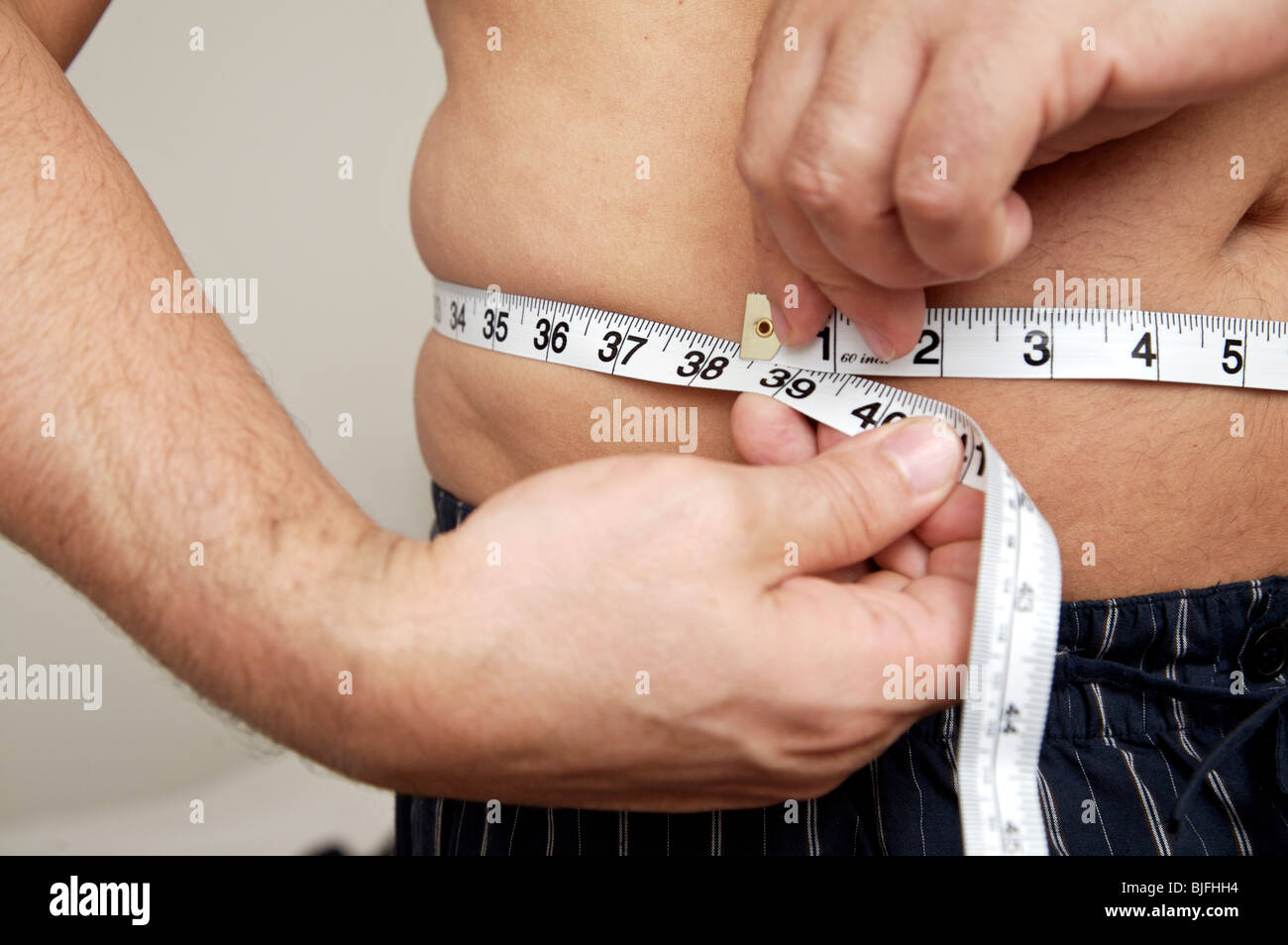 close-up-of-man-measuring-waist-with-tap
