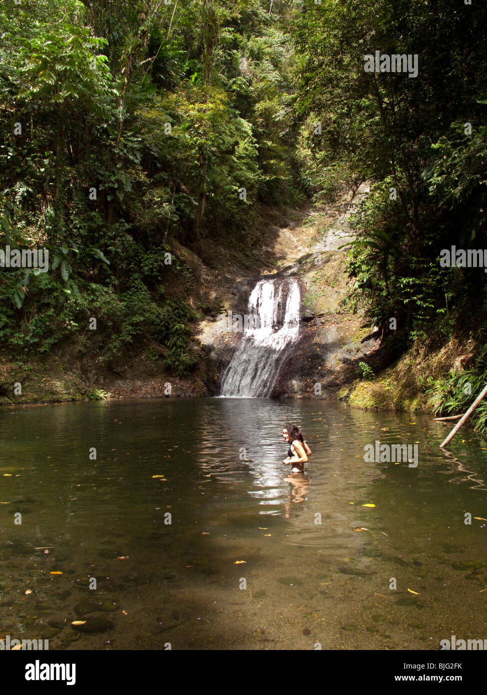 Girl bathing in river near waterfall situated in Caribbean ...