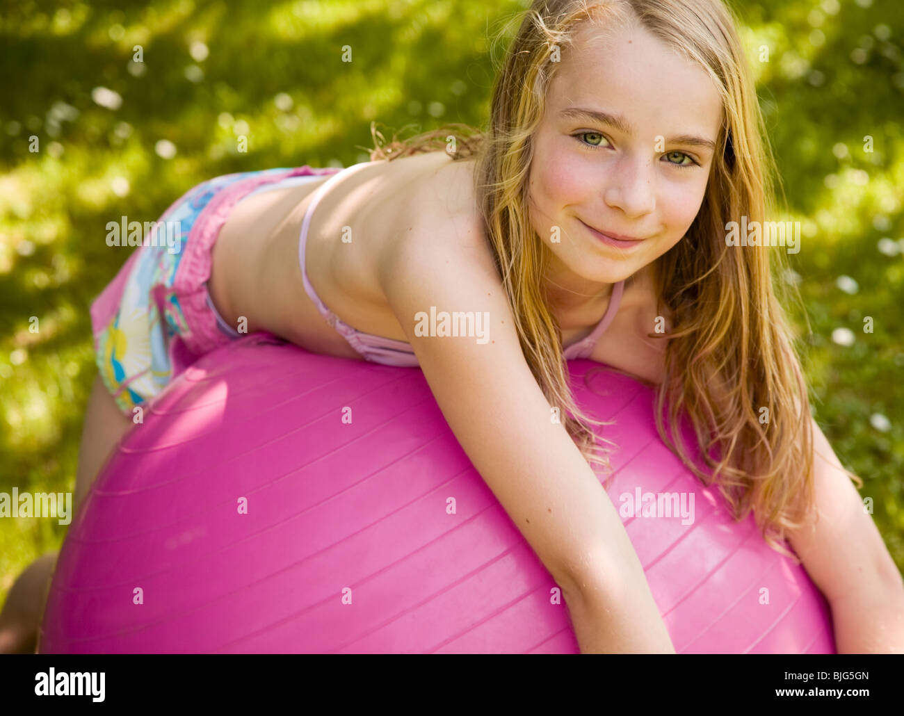 Portrait of young blonde girl lying on pink ball smiling ...
