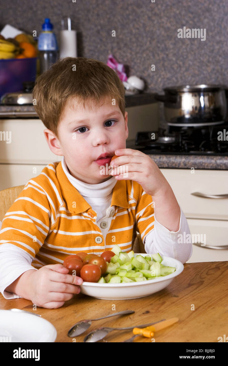 Little boy fetching healthy green food eating tomatoes for Food bar hands