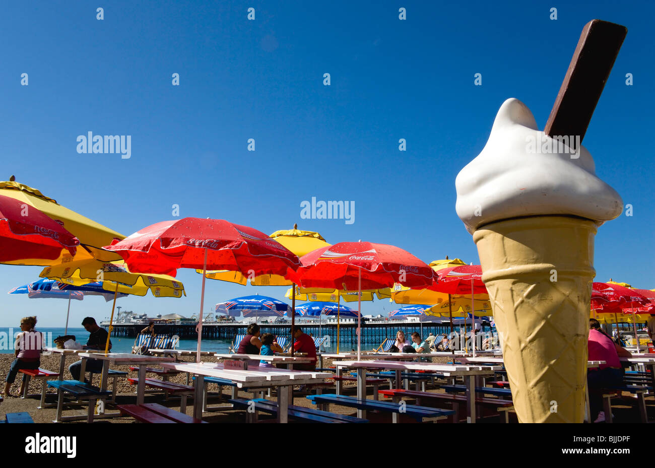 england east sussex brighton the pier with people under sunshade umbrellas by tables: metre giant umbrella
