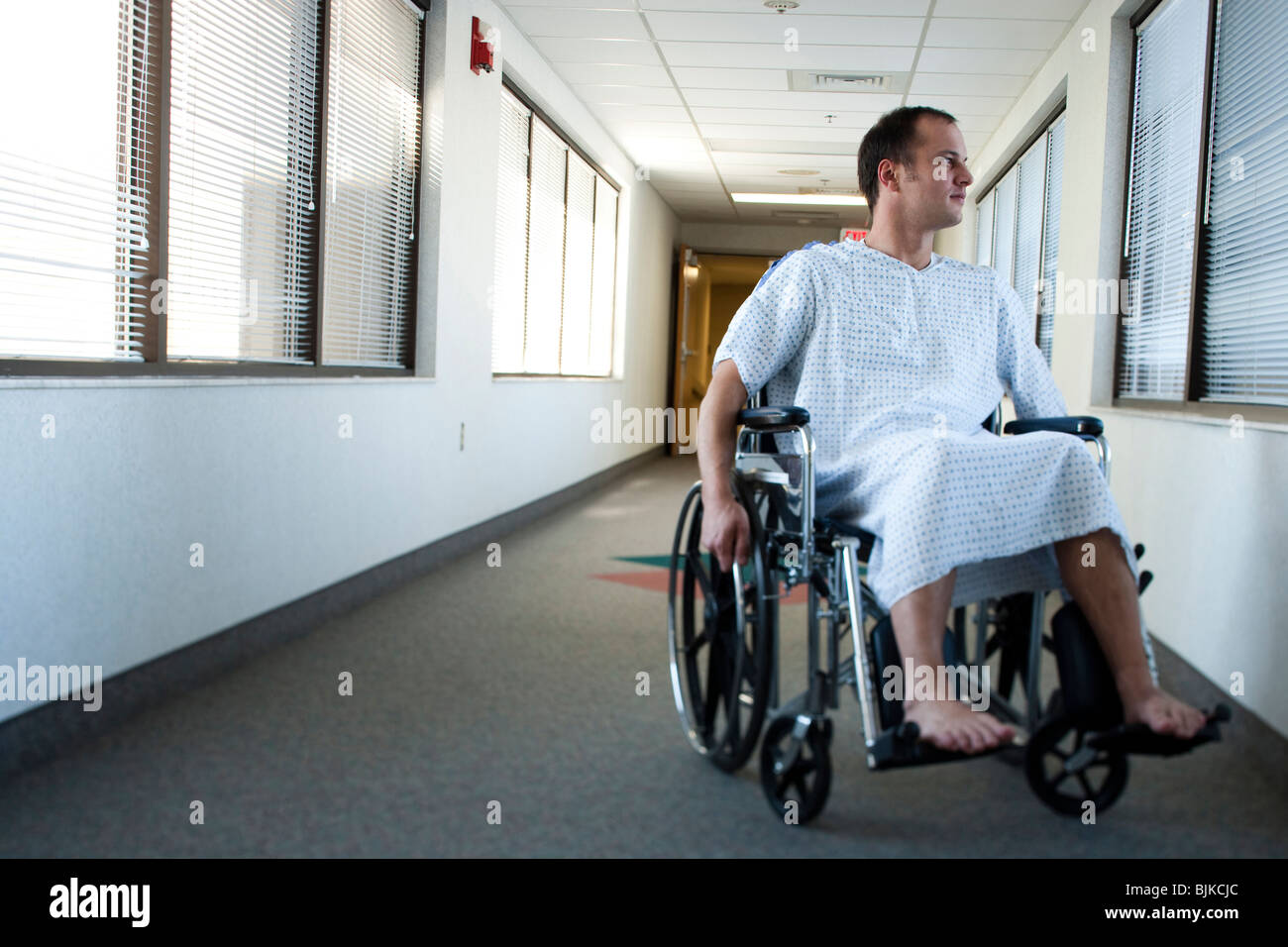 Man in hospital gown in wheelchair in corridor with for Wheelchair accessible homes for sale near me