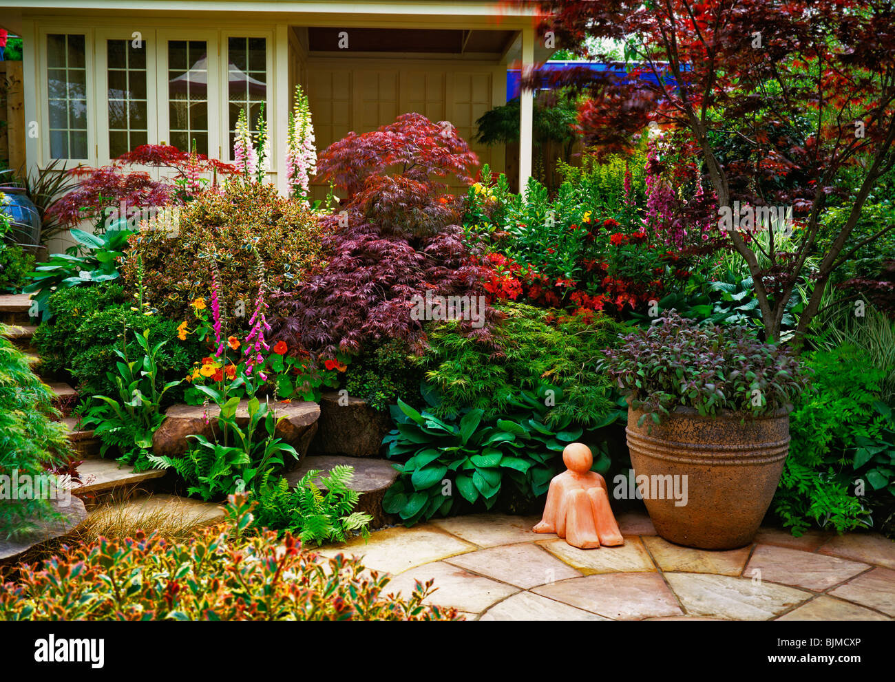 A Back Garden With A Patio And Circular Terrace With Containers And  Colourful Shrubs   Stock