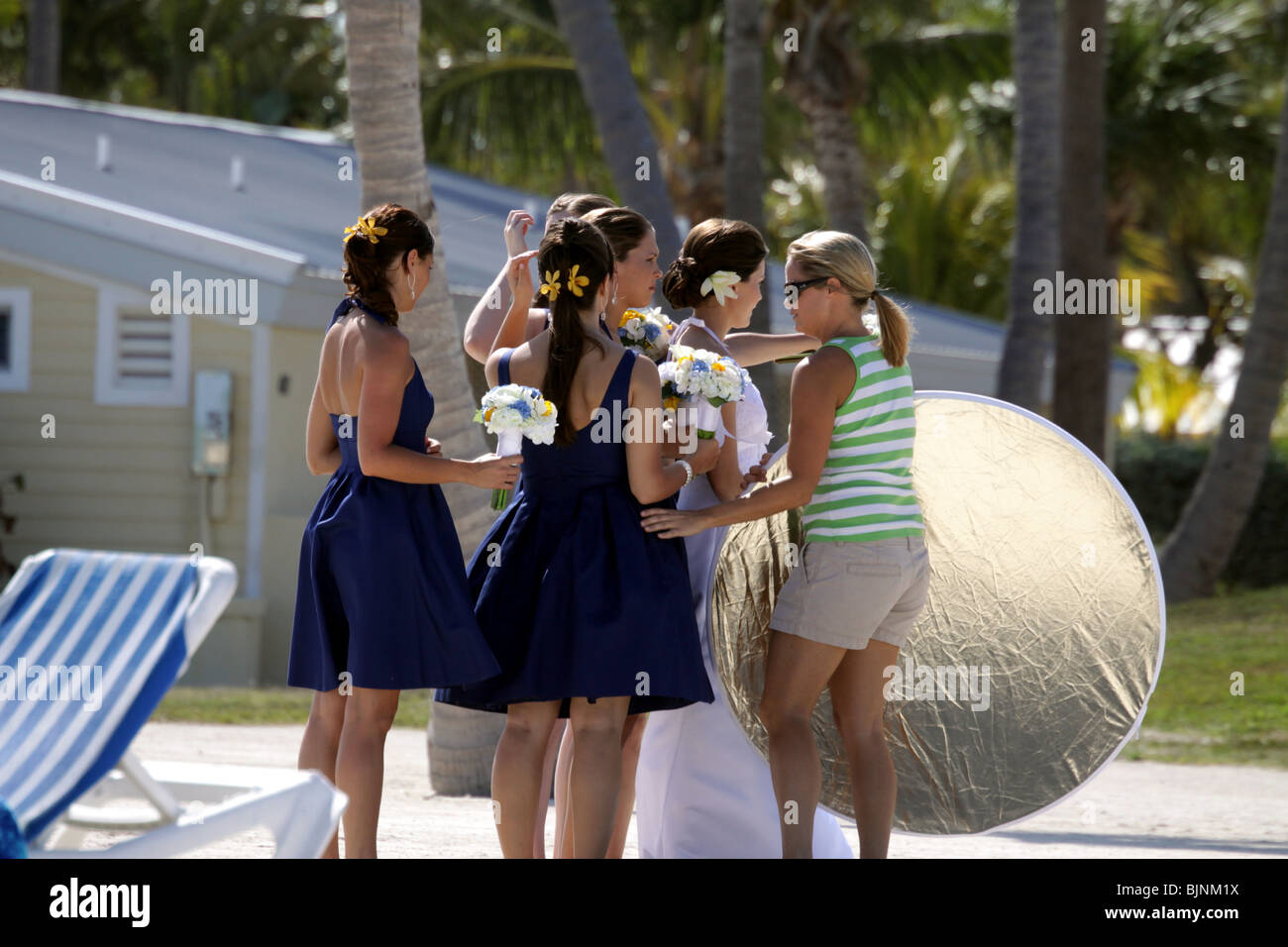 A Photography Assistant Helping Bride And Her Bridesmaids Get Ready For Wedding Photos On The Beach In Florida Keys