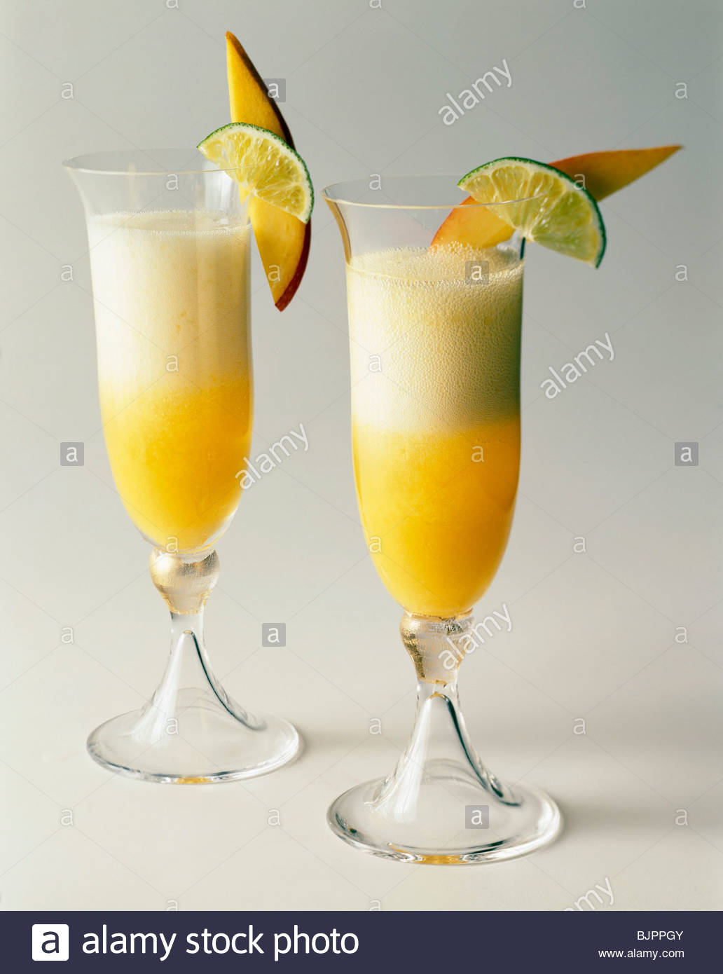 Two champagne cocktails with fruit garnish on a white for Champagne drinks with fruit
