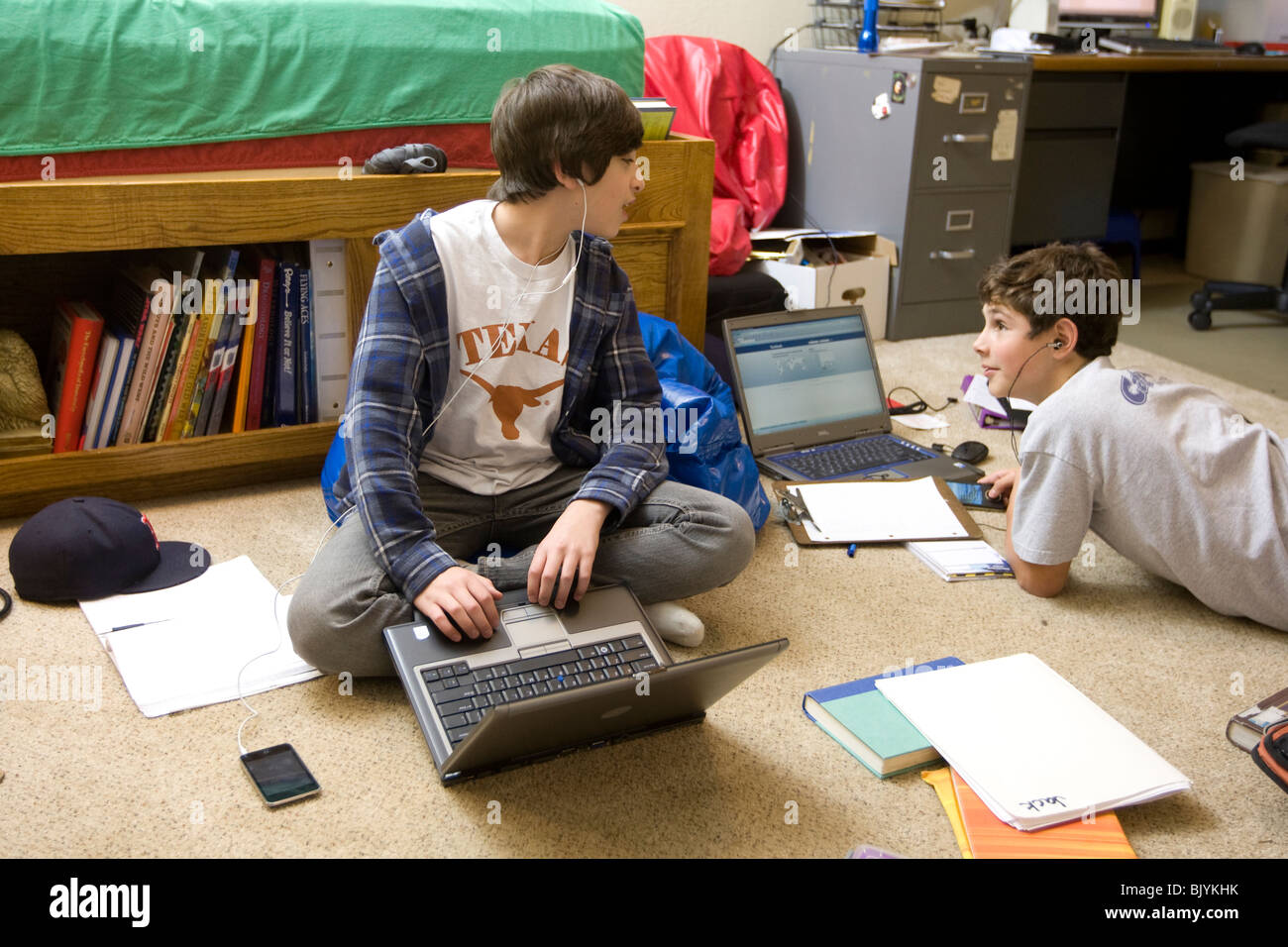 Teen boys in bedroom with laptop computer and textbooks, listening to iPod  and MP3 players with earbuds, and texting friends