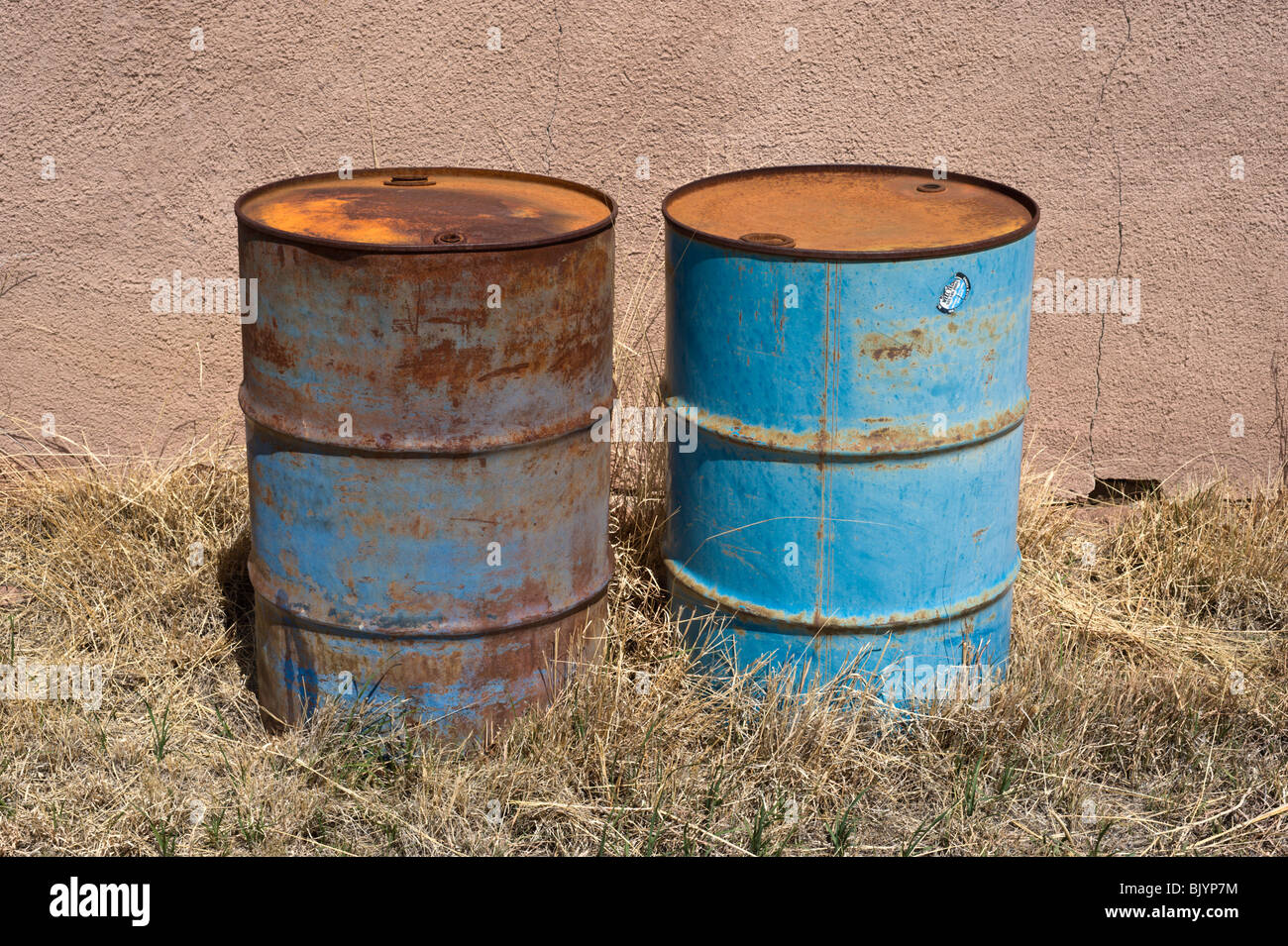 two blue 55 gallon drums sit rusting in front of an adobe wall in billy the