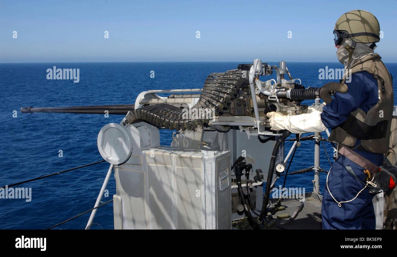 U.S. Navy Gunner's Mate fires a .50-caliber machine gun during ...