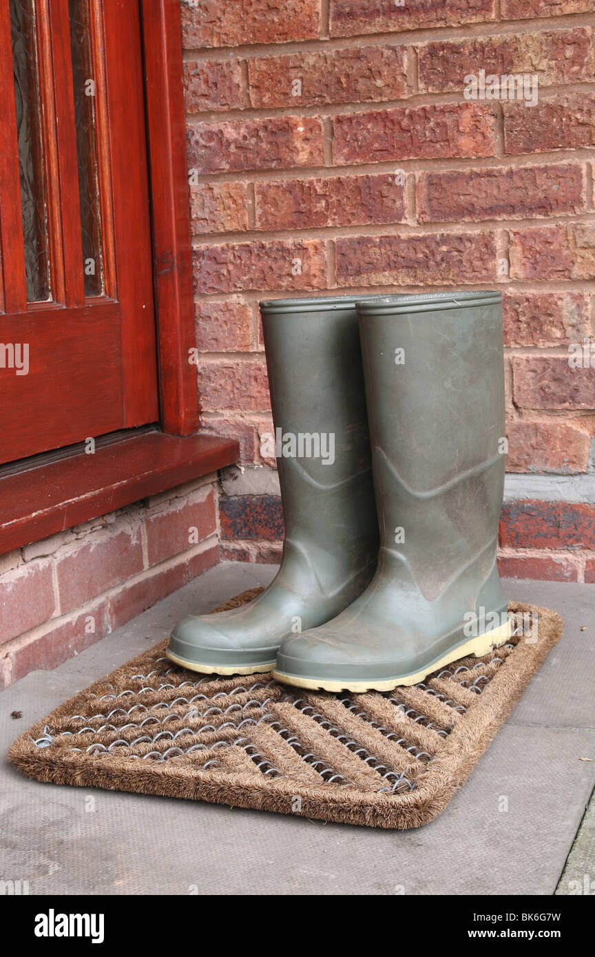 green wellington boots on door mat by front door outside