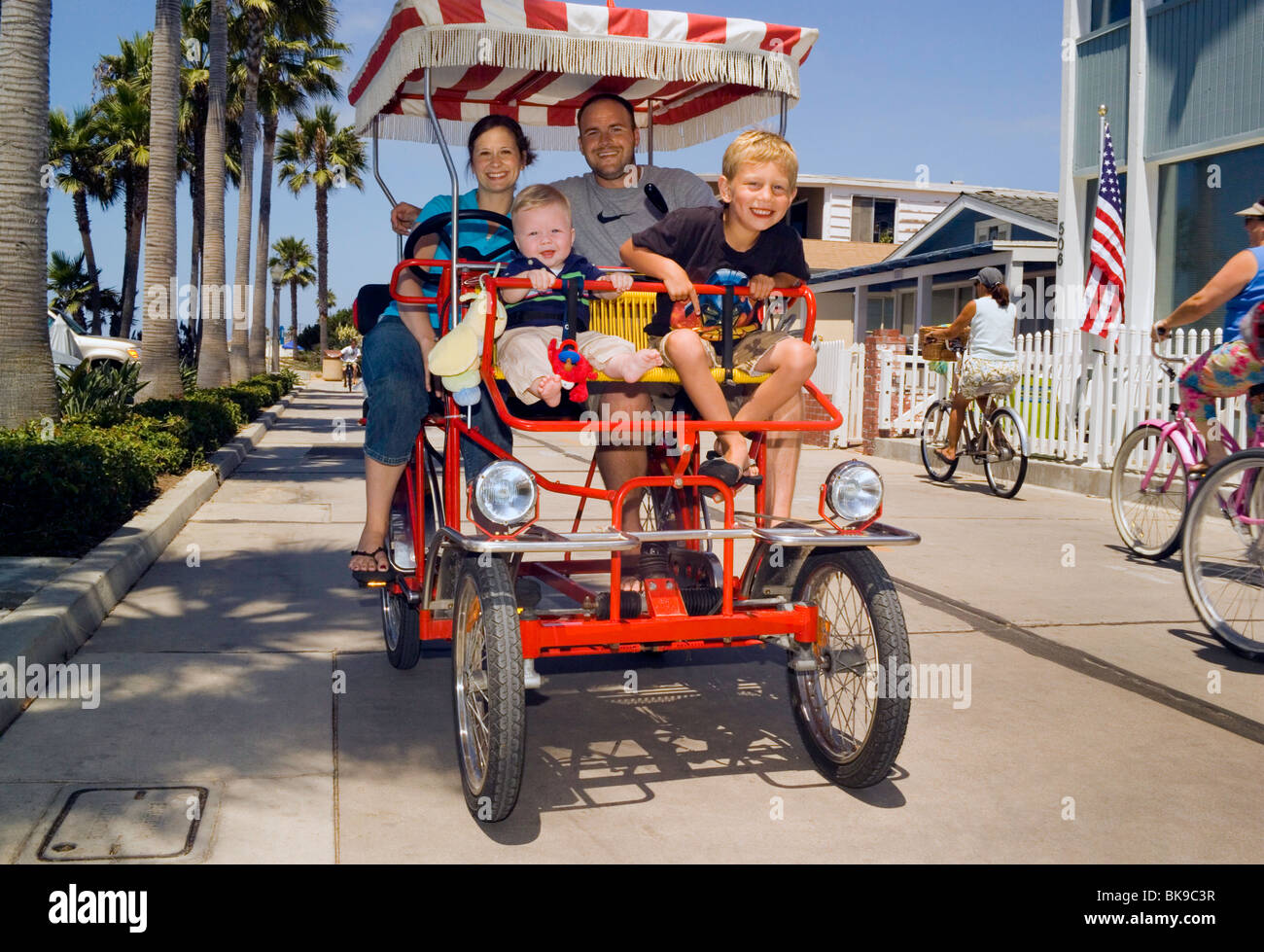 A Vacationing Family Pedal Their Four Person Rental Surrey Bike