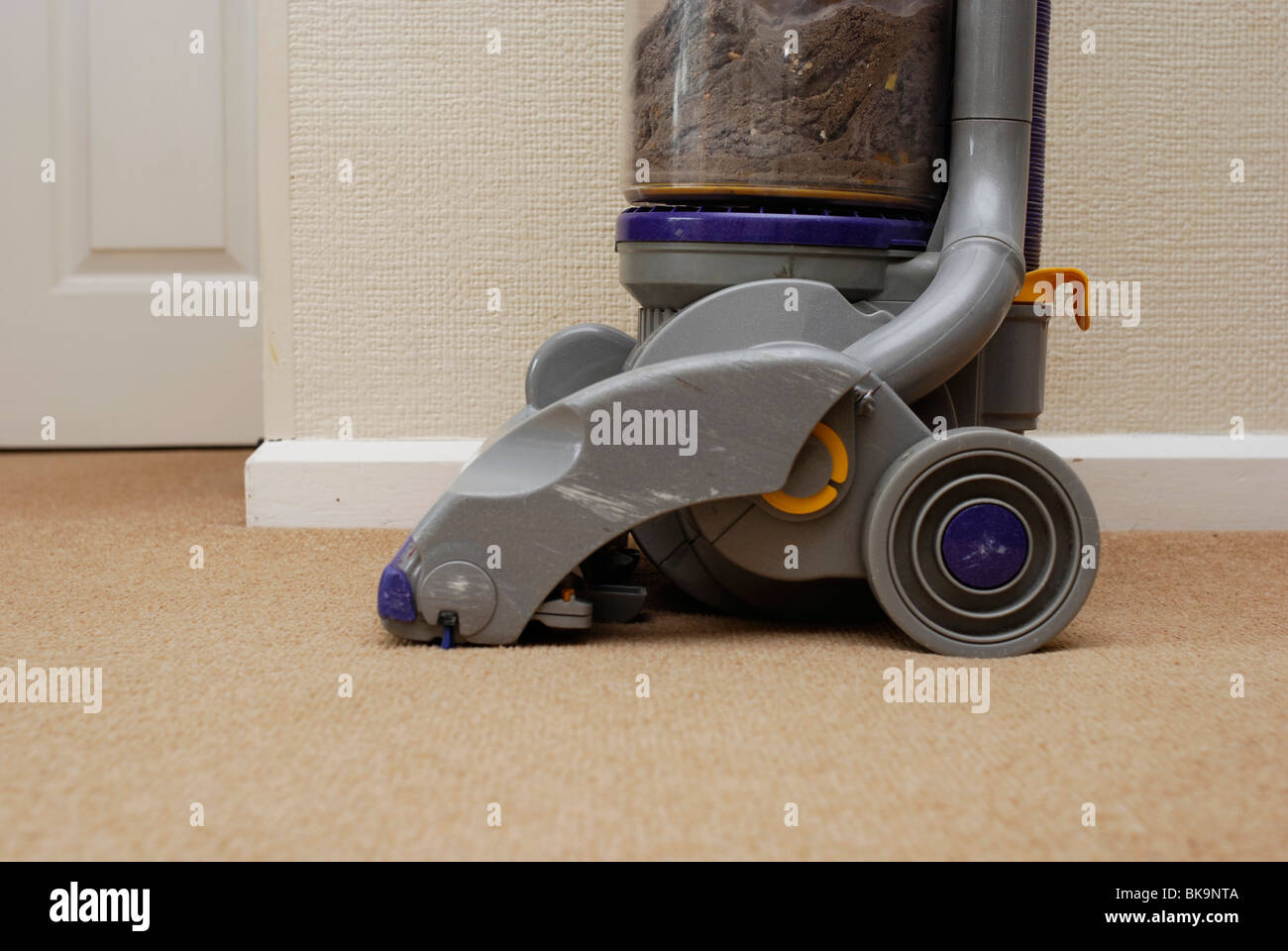 dyson vacuum cleaner on lounge carpet with dust and dirt visible inside cleaner stock - Dyson Vacuum Cleaner