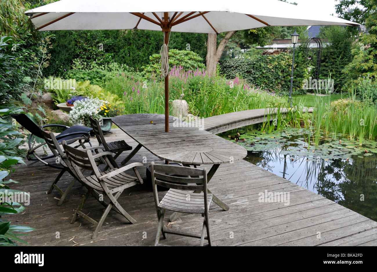wooden decking area with seats at a swimming pond stock photo