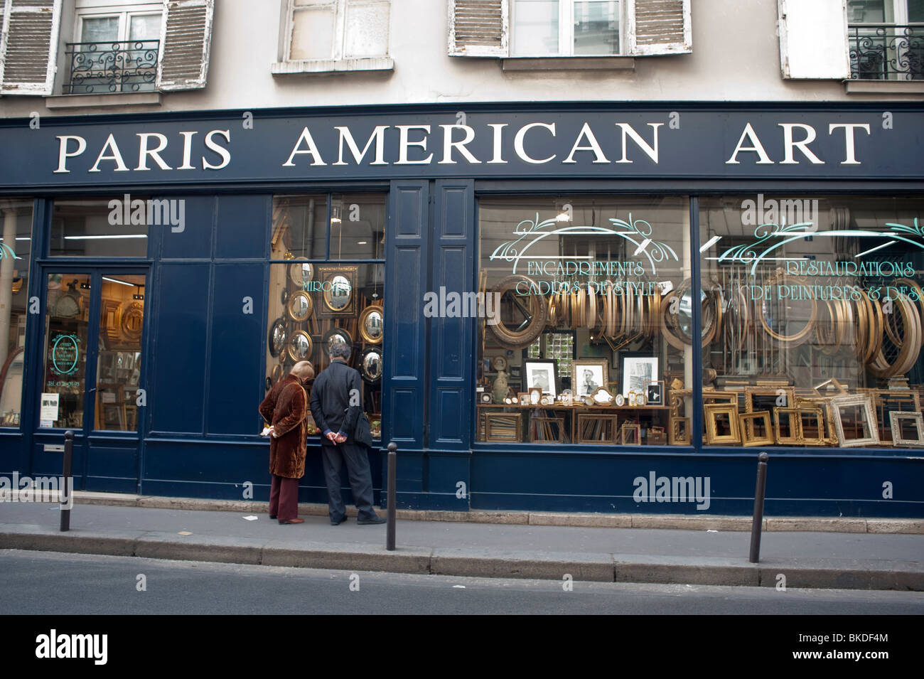 couple window shopping picture framing store in latin quarter paris american art seniors outside storefront shop front name has now been changed