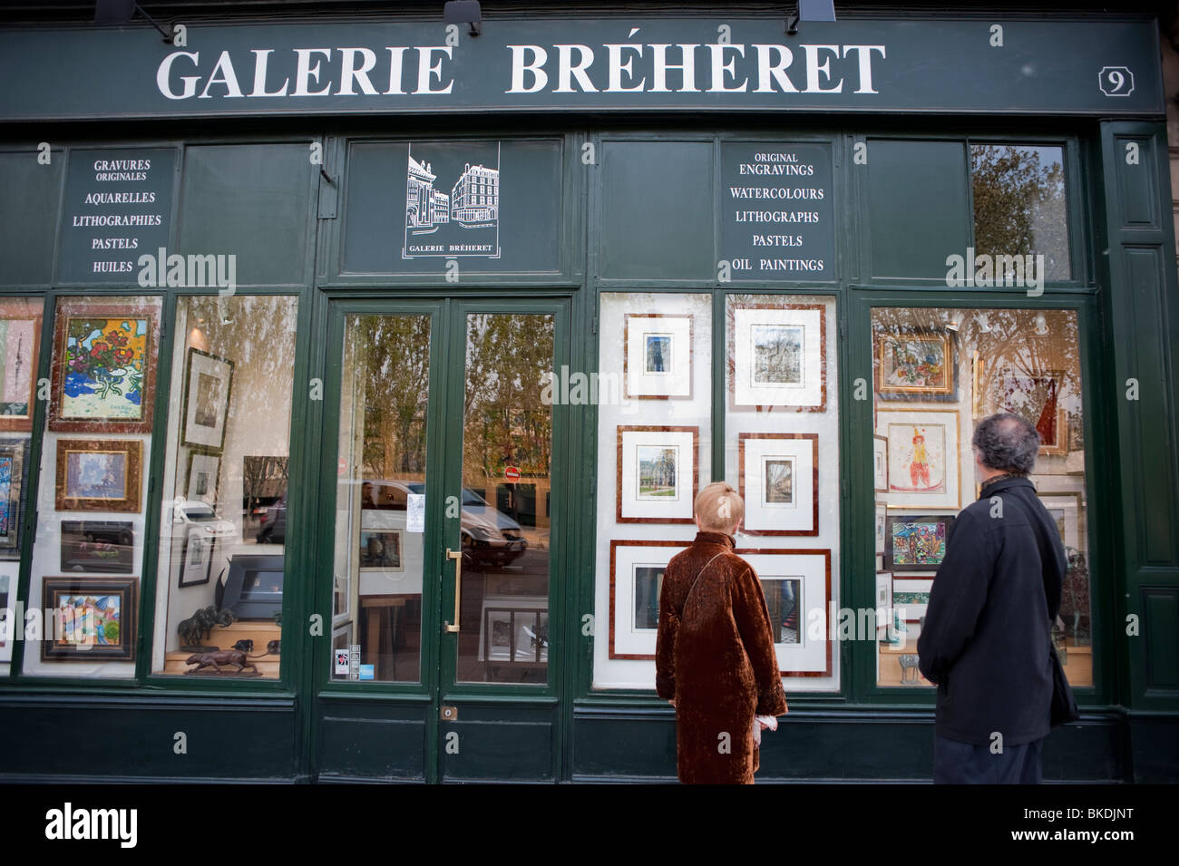 paris france couple window shopping at picture framing store in latin quarter galerie breheret outside shop front saint germain des prs