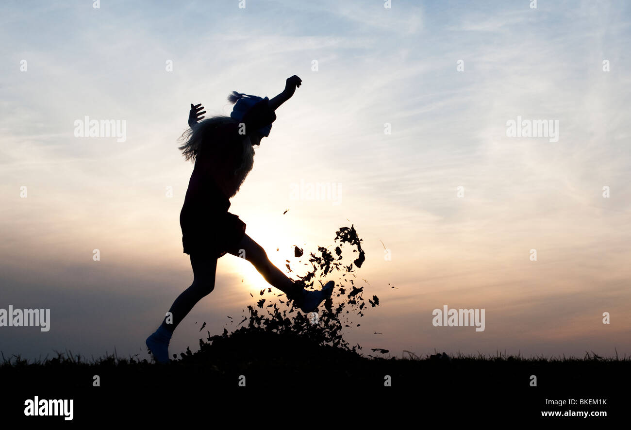 http://c8.alamy.com/comp/BKEM1K/young-girl-energetically-having-fun-kicking-a-pile-of-leaves-silhouette-BKEM1K.jpg