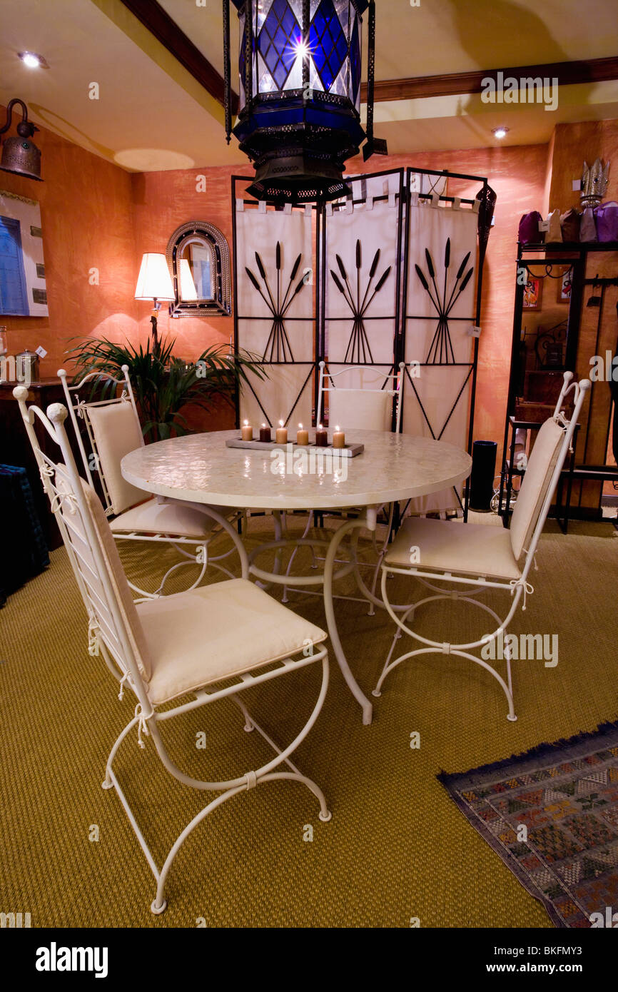 Glass And Metal Lantern Above White Metal Table And Chairs In Moroccan Style  Dining Room With Folding Screen