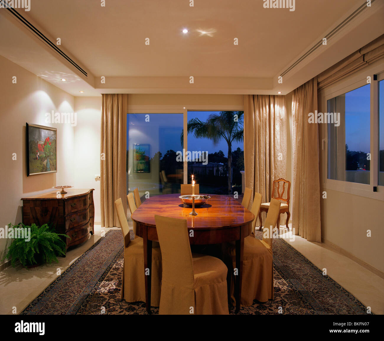 Down Lighting In Modern Spanish Dining Room At Night With Patio Doors And Polished Wood Table Chairs Loose Covers