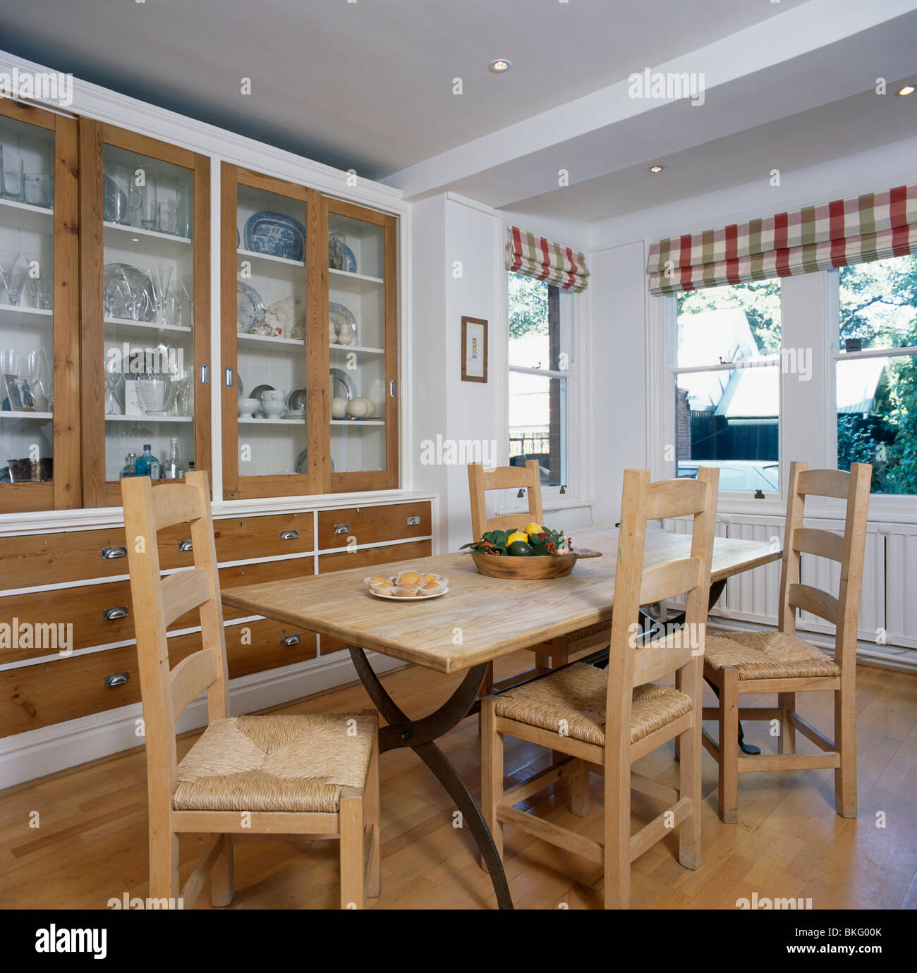 Pale Wood Table And Rush Seated Chairs In Modern White Dining Room Extension With Fitted Dresser Glazed Doors