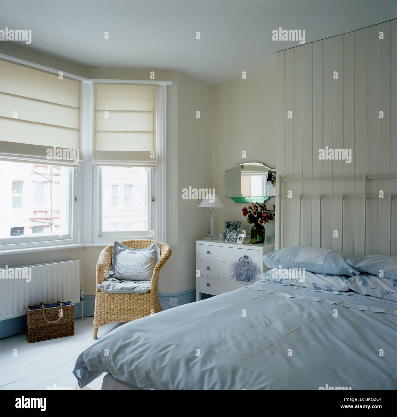 Bed in bay window - Stock Photo Wicker Armchair In Front Of Bay Window With Cream Blinds In Townhouse Bedroom With Bed With Pale Blue Bedlinen