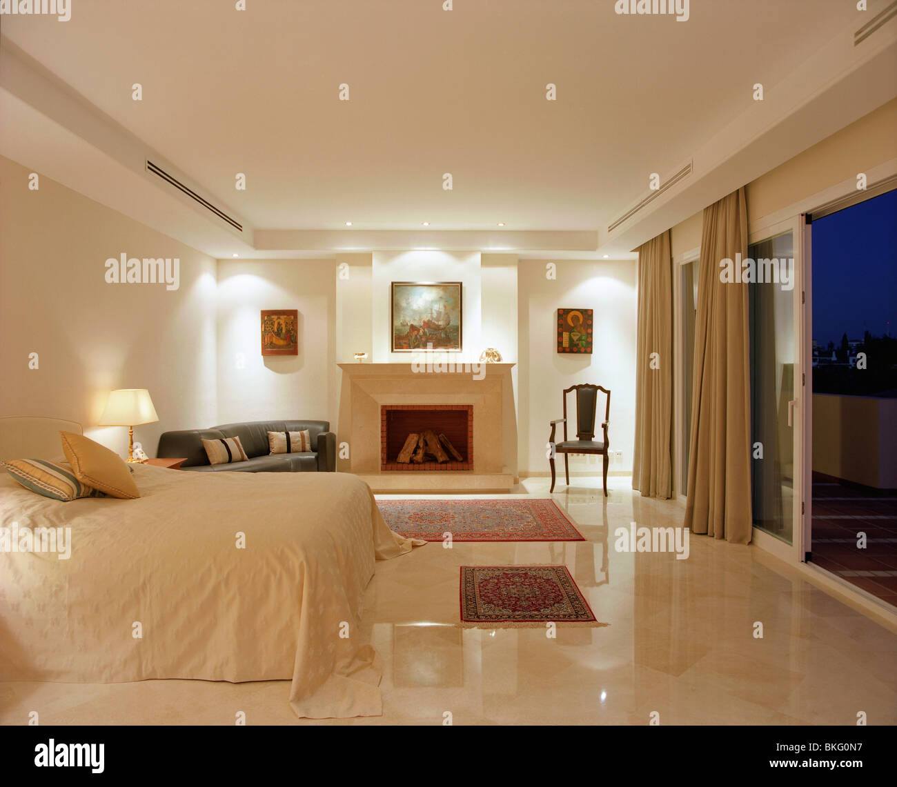 Down Lighting In Modern Cream Bedroom With Marble Floor Fireplace And Bed Cover