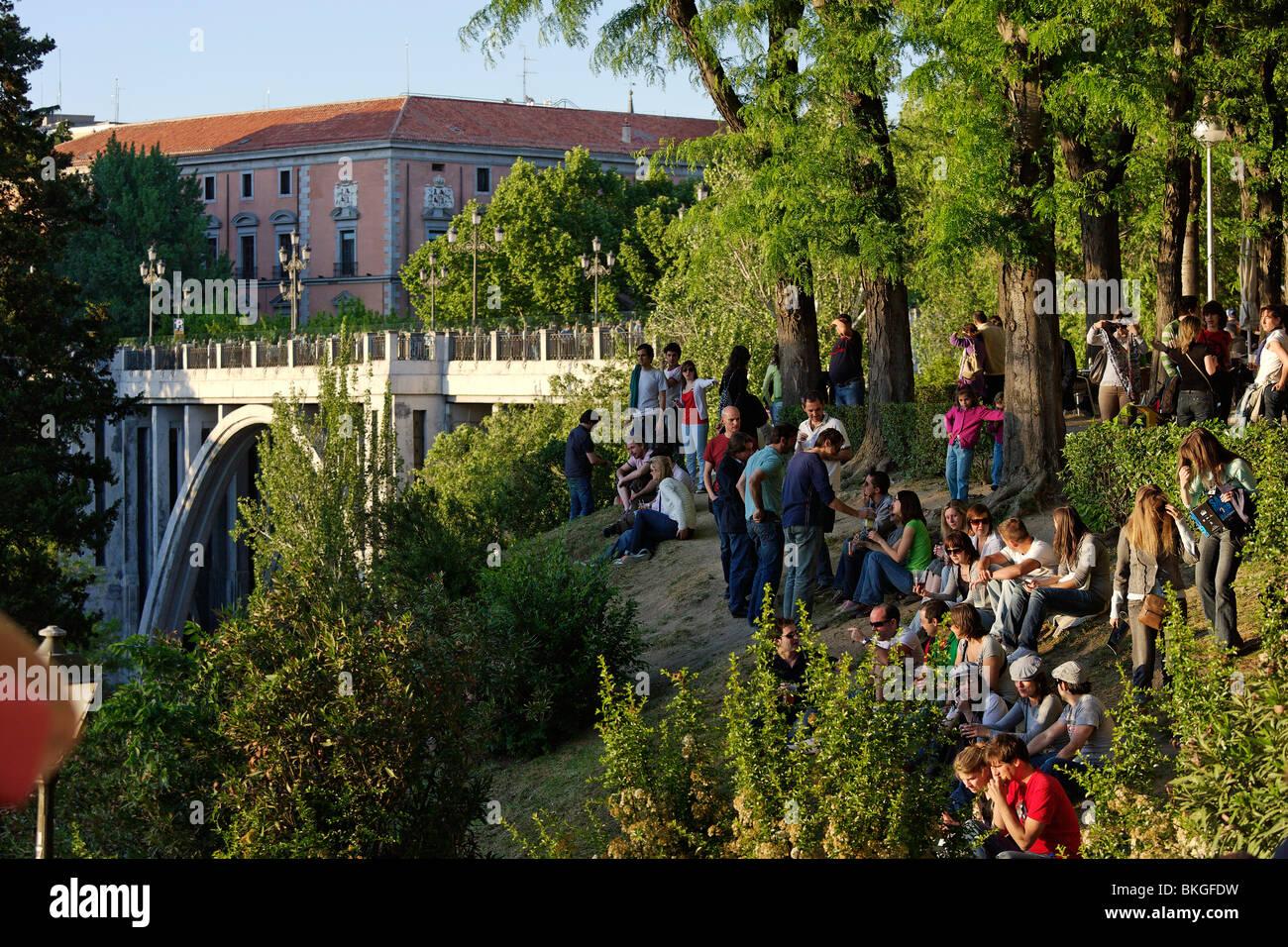 People sitting on grass near a viaduct jardines de las for Jardines de las vistillas