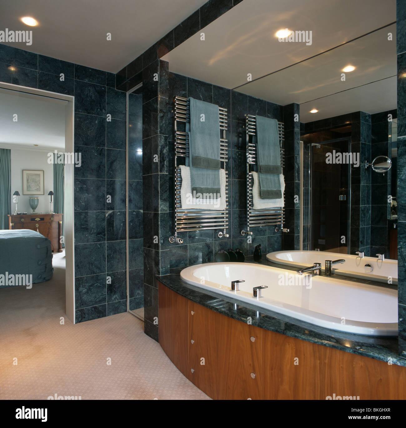 Towel rails for bathroom - Stock Photo Towels On Heated Towel Rails Above Bath In Modern Marble Tiled En Suite Bathroom
