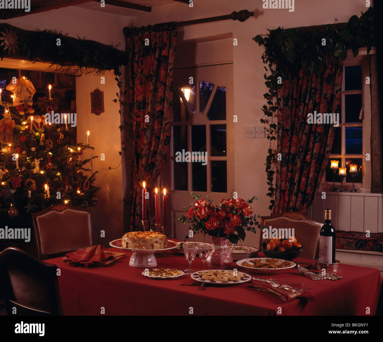 Red Cloth On Table Set For Christmas Tea In Cottage Dining Room With Fairy Lights Tree And Heavy Curtains Window