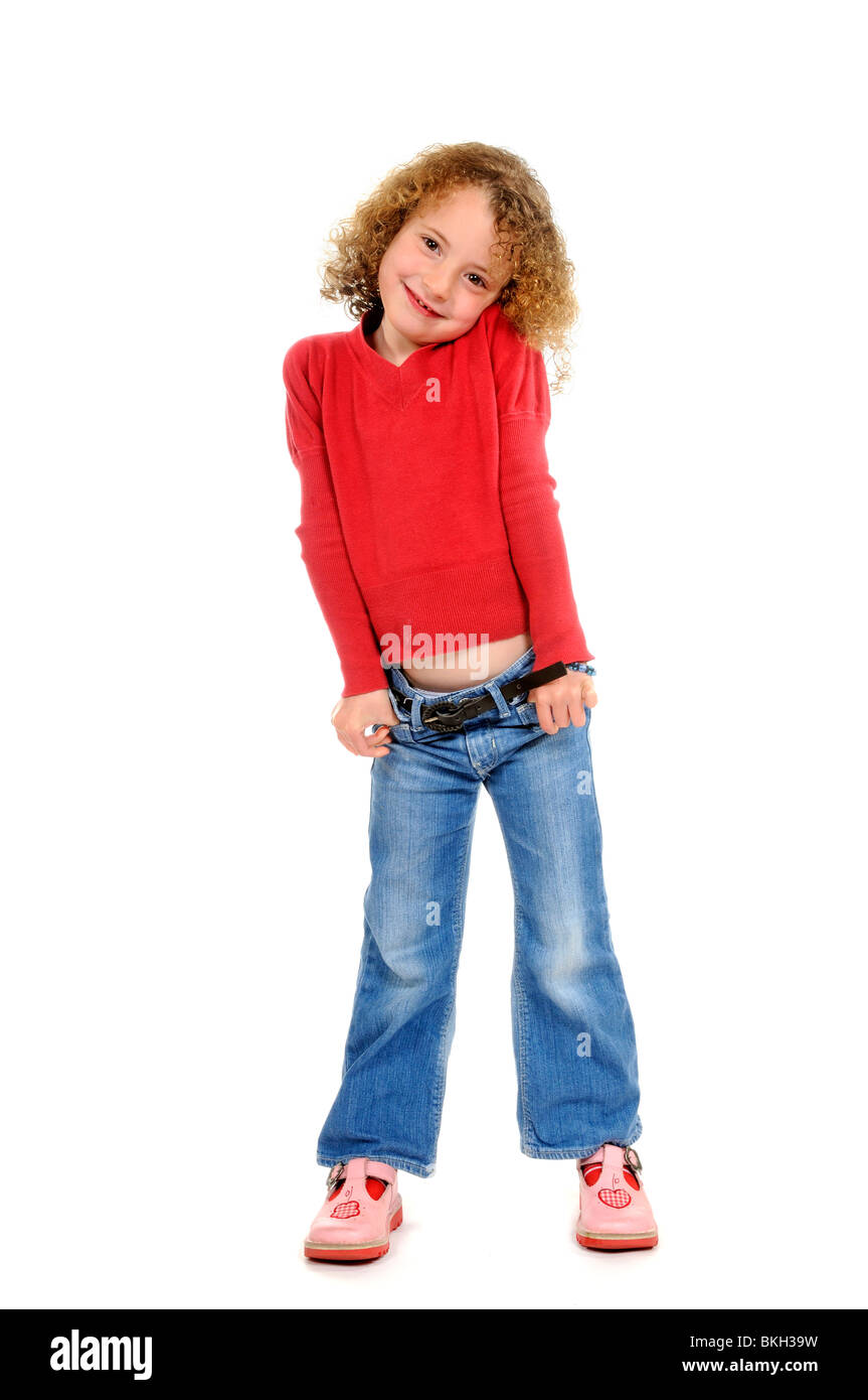 Six year old girl wearing blue jeans & a red shirt with sandals ...