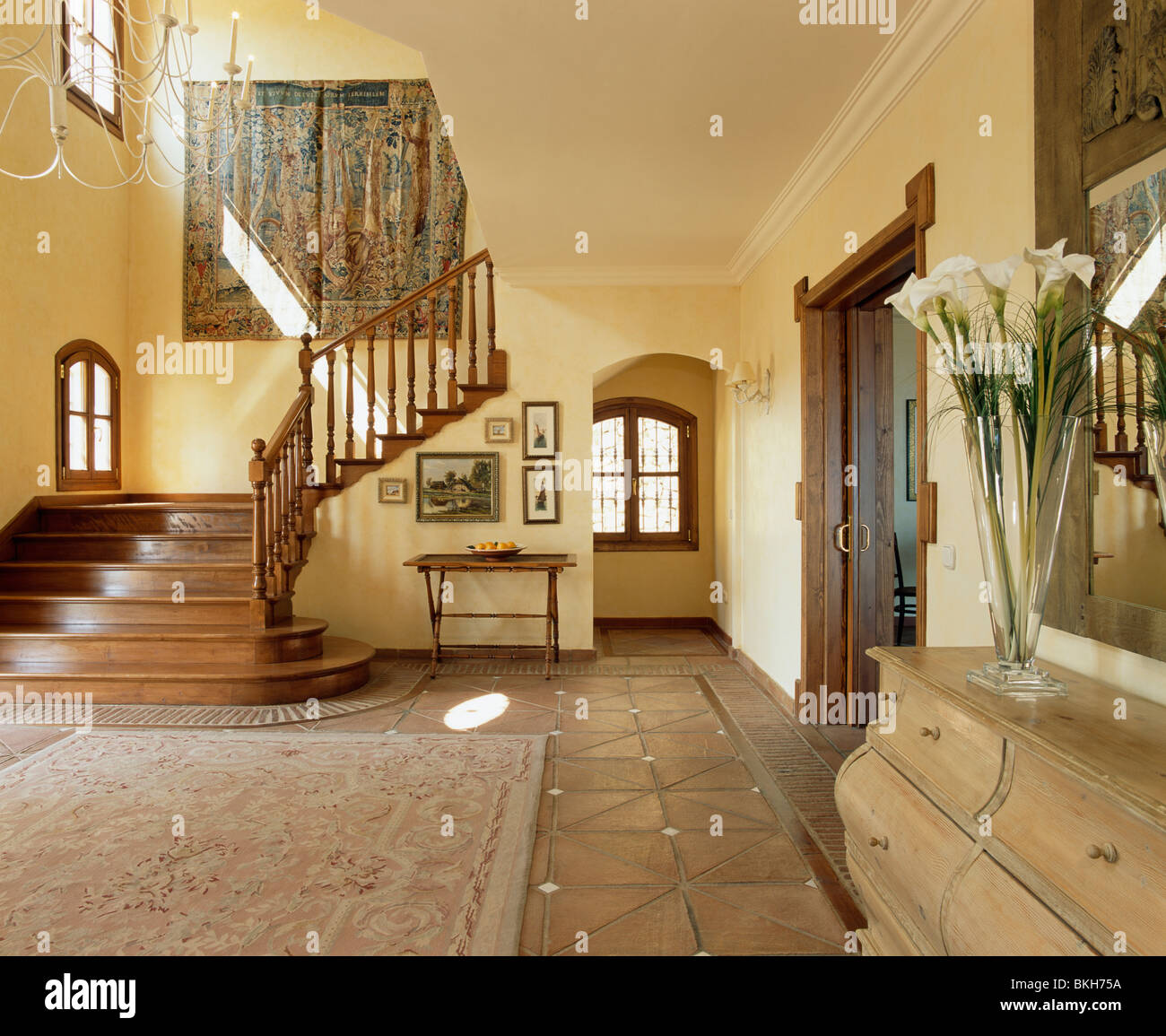 Patterned rug on terracotta floor tiles in large traditional patterned rug on terracotta floor tiles in large traditional spanish hall with tapestry on wall above wooden staircase dailygadgetfo Choice Image