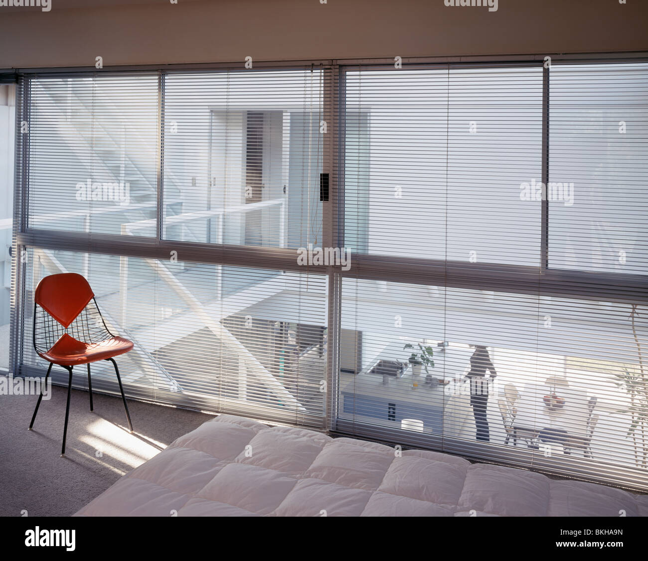 Charles Eames Chair In Front Of Glass Wall With Blinds In Modern White  Bedroom Overlooking Open