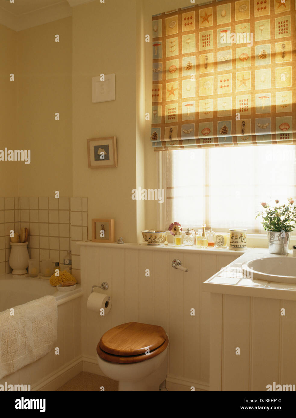 toilet with wooden seat below window with osbornelittle neutral blind in small cream bathroom