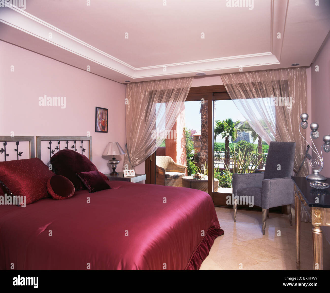 Red Satin Bedcover On Bed In Modern Bedroom With Metallic Voile Curtains  On Patio Doors To Balcony