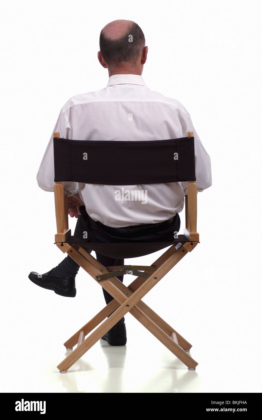 Back of director chairs - Rear View Of Smartly Dressed Mature Man Sitting In A Directors Chair Isolated