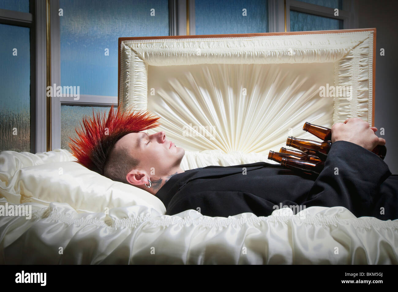 a deceased young man in a coffin holding beer bottles