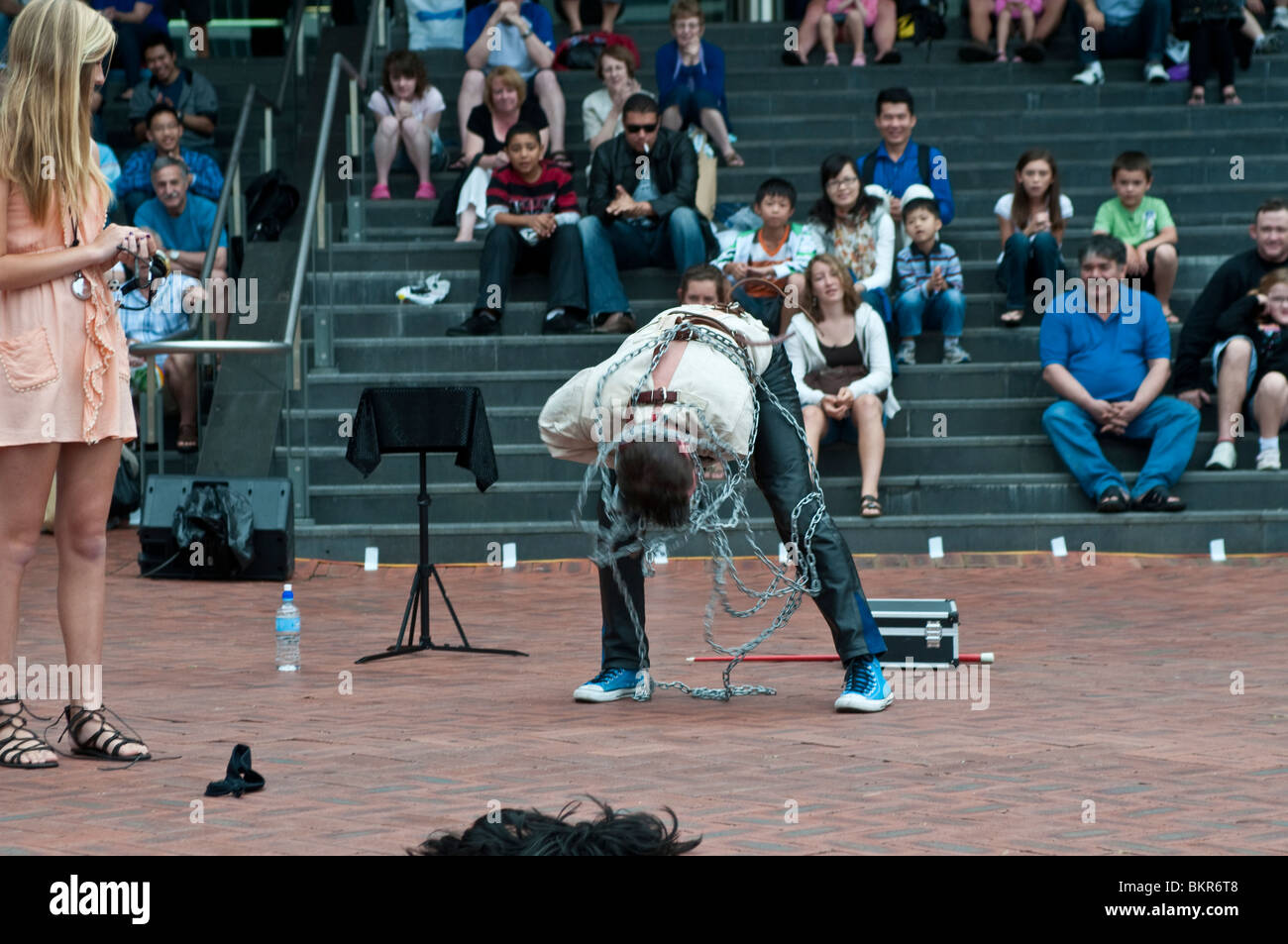 Performer getting out of straight jacket and chains, Street ...