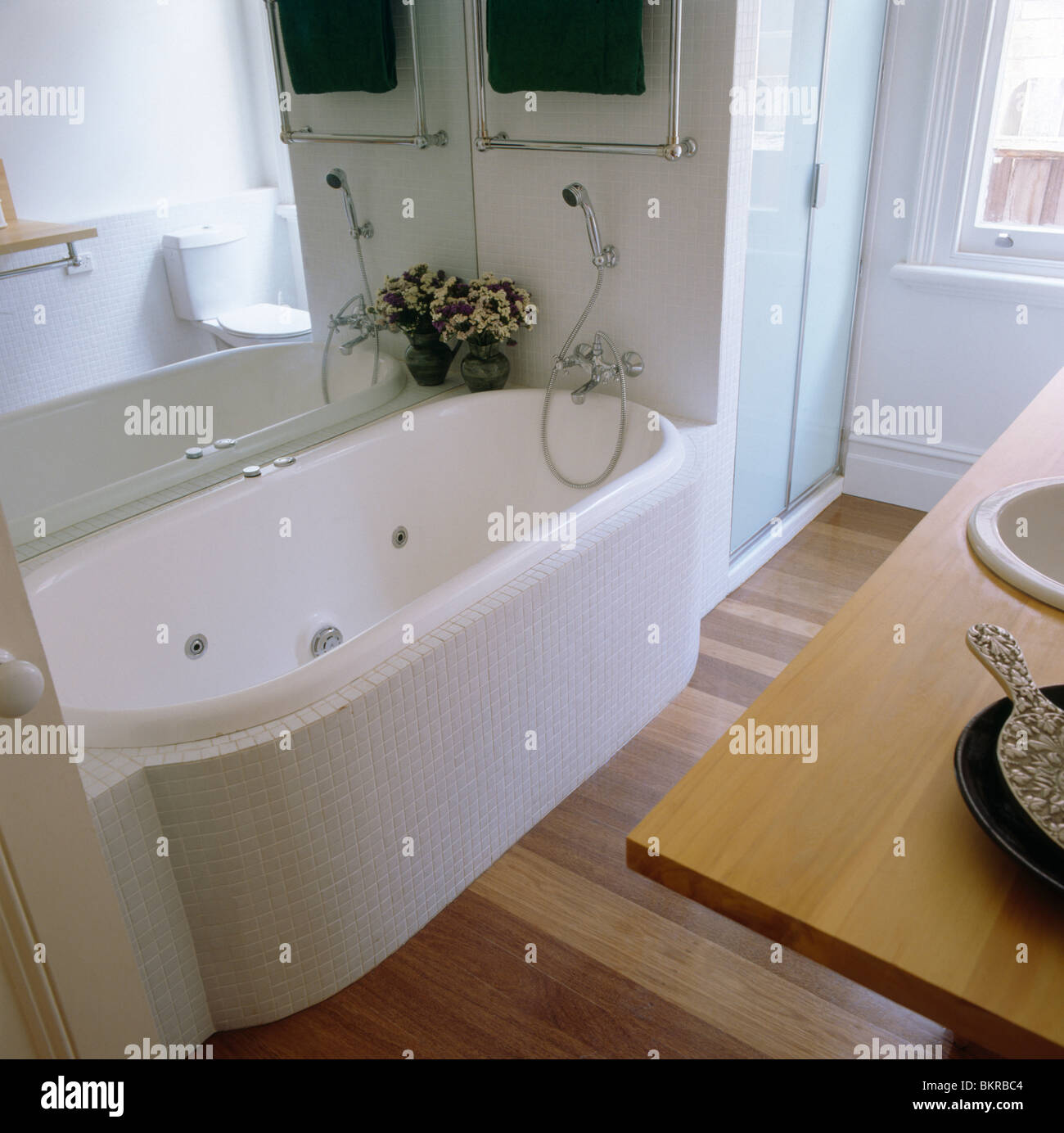 Large mirror above bath with white mosaic surround in modern white ...