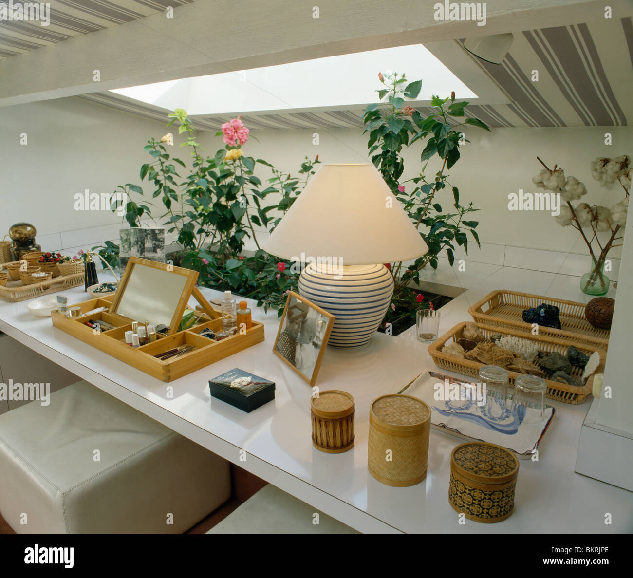 Close up of lighted lamp beside wooden cosmetic storage box on white table with cylindrical wooden boxes in attic bathroom. Close up Of Lighted Lamp Beside Wooden Cosmetic Storage Box On