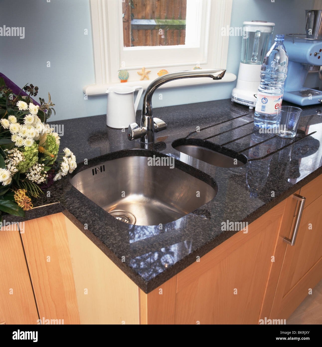 Kitchen with close-up of under-set stainless steel sink in black ...