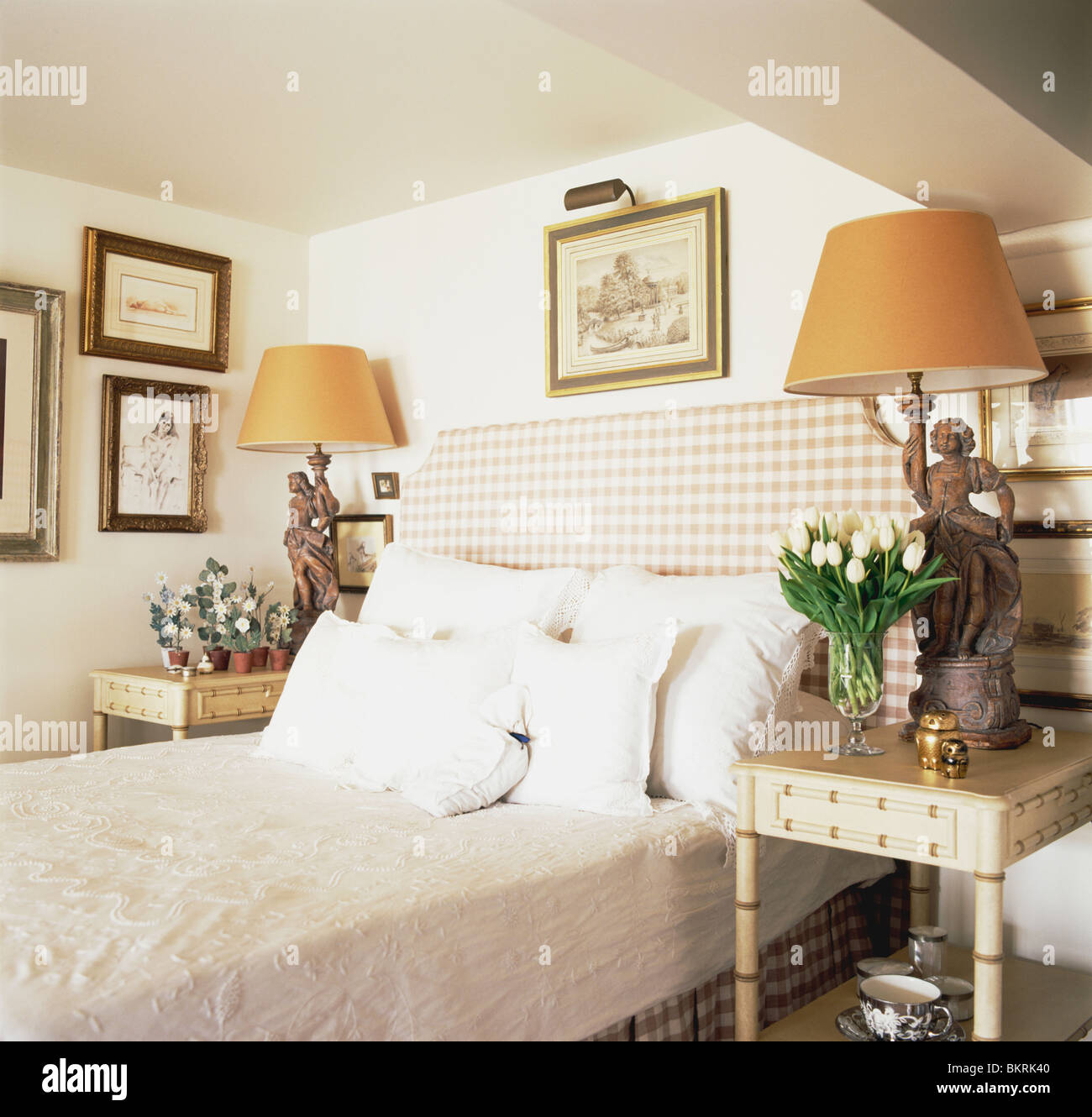 White pillows against checked headboard on bed in small cottage bedroom  with orange lamps on tables on either side of bed