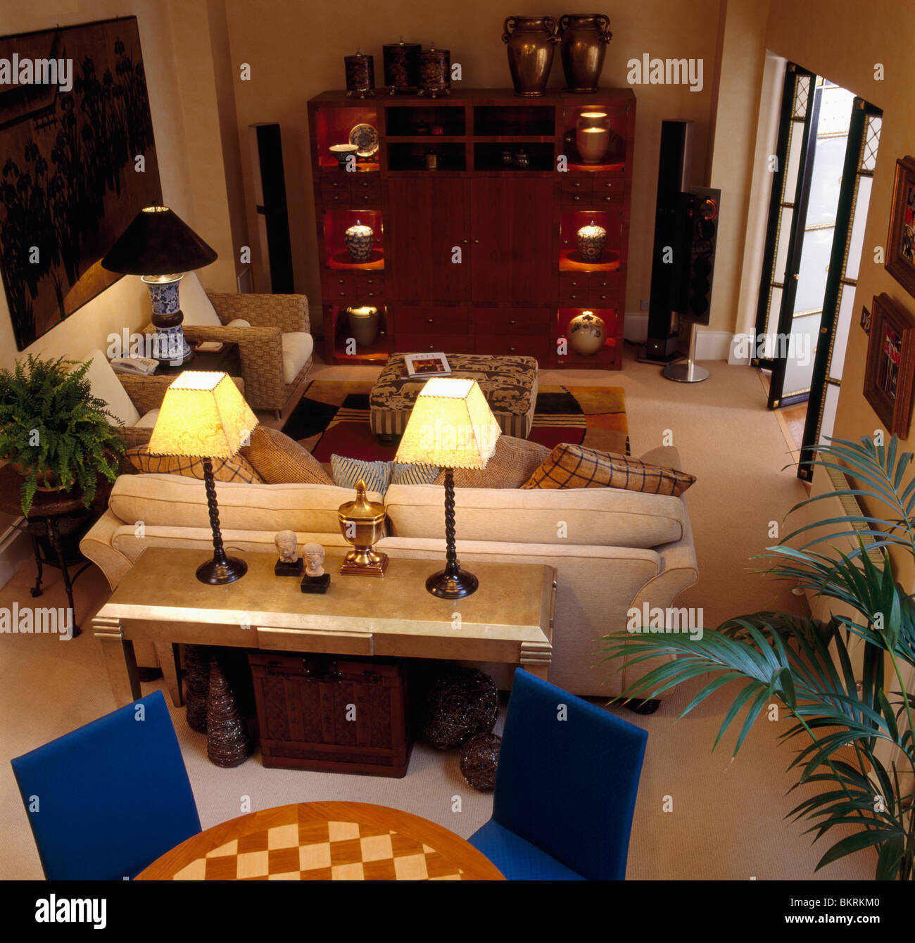 Birdseye View Of Lighted Lamps On Console Table Behind Beige Sofa - Console behind sofa