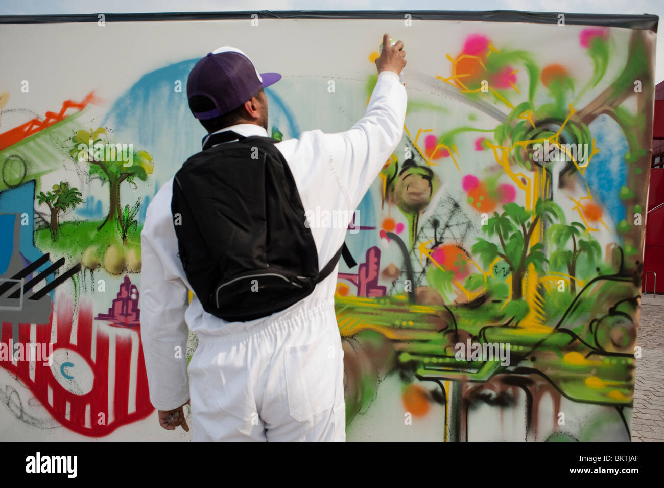 stock photo man spray painting wall mural graffiti at construction. Black Bedroom Furniture Sets. Home Design Ideas