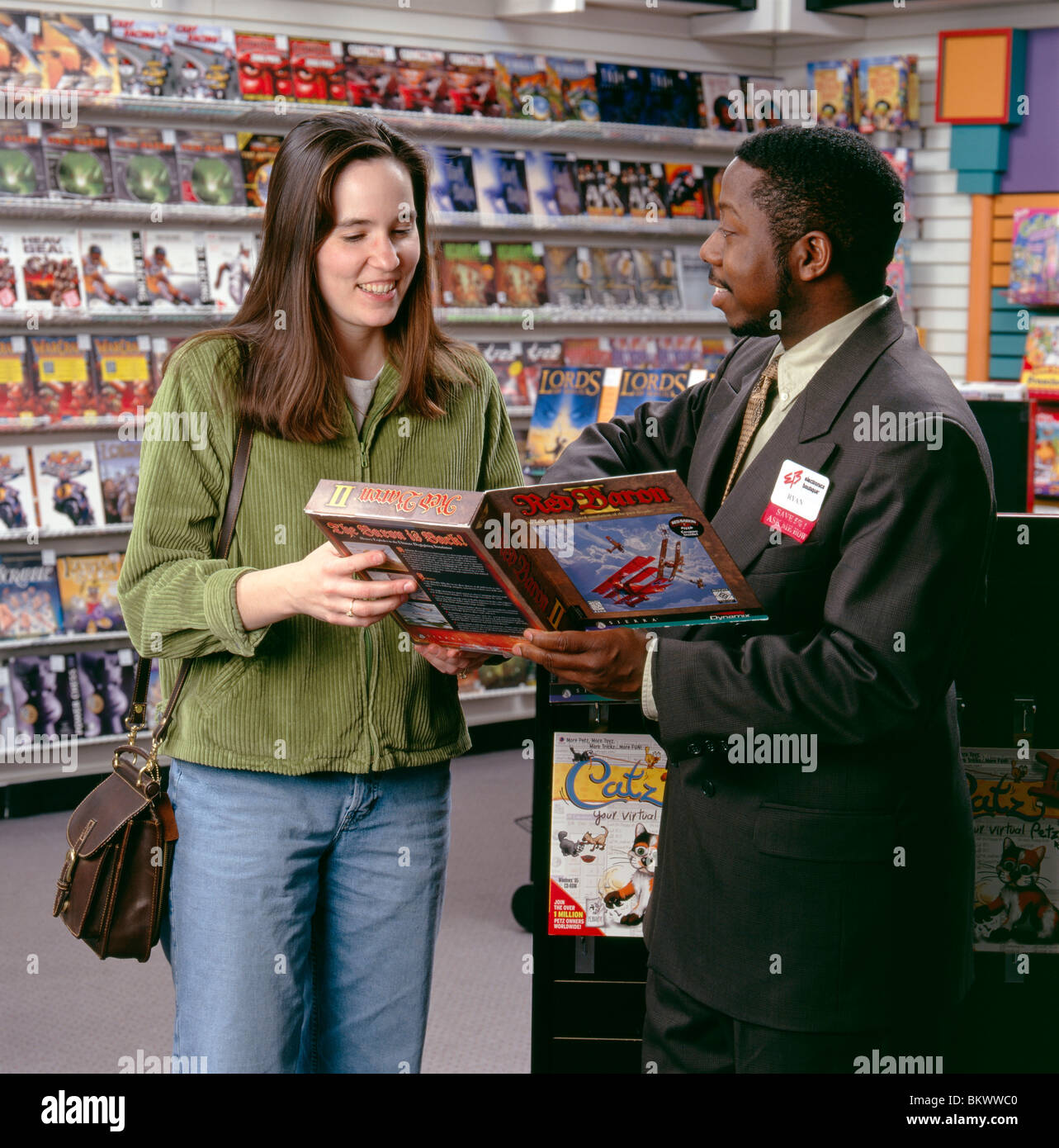 male african american s clerk showing a female customer a male african american s clerk showing a female customer a gaming software package in a retail store
