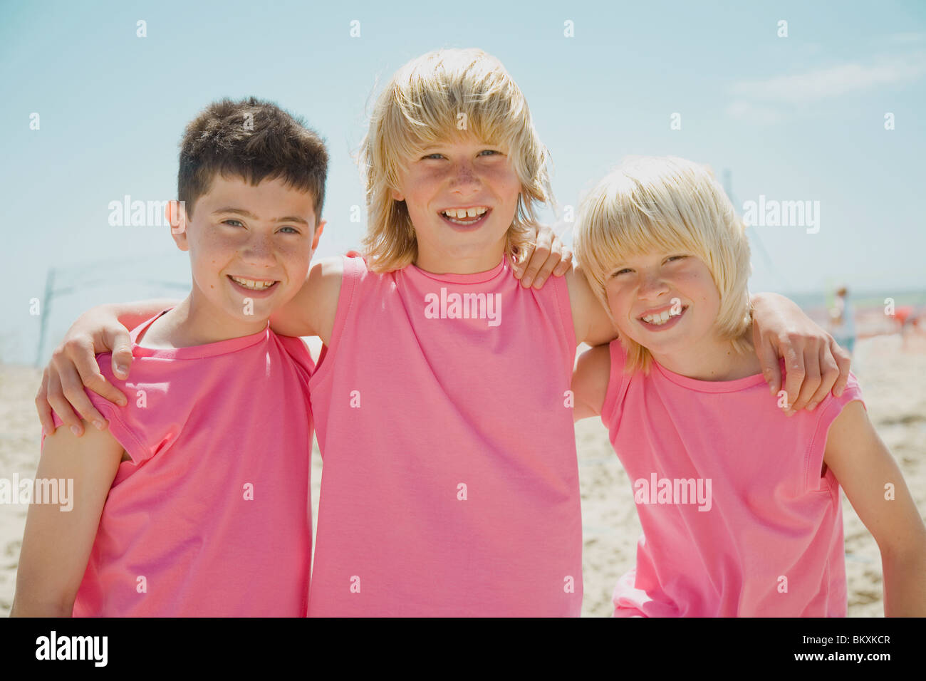 Three smiling boys on a beach wearing identical pink t-shirts ...